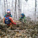 Kinder sitzen an einem nebeligen und reifigen Tag im Wald auf einem Baumstamm