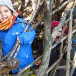 Kinder schauen hinter einem aus Ästen hergestellen Zaun hervor