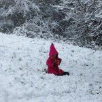 Ein Kind in rotem Overall mit spitzer Kapuze sitzt mitten im Schnee