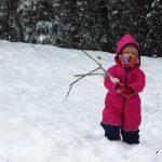 Ein kleines Kind in rotem Overall und Schal ums Gesicht steht mit Stecken in der Hand im tiefen Schnee