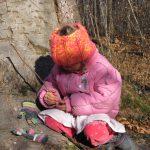 Ein Mädchen sitzt neben einem Baumstamm und spielt mit kleinen Ästen