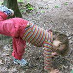 Ein Kind in bunt-gestreifter Kleidung versucht am Waldboden einen Handstand zu machen