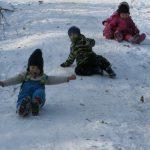 Kinder rutschen auf dem Schnee einen Hang hinunter