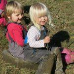Kleine Kinder sitzen auf Steinen und spielen in der Wiese