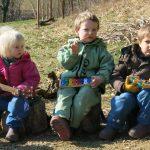 Drei Kinder sitzen nebeneinander auf Holzstämmen in der Wiese und spielen auf ihren Instrumenten