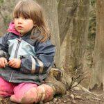 Mädchen kniet am erdigen Waldboden und blickt in die Ferne