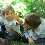 Drei Kinder unterhalten sich sitzend am Waldboden