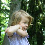 Ein blondes, lächelndes Mädchen verschränkt ihre Arme seitlich auf Wangenhöhe