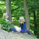 Zwei blonde Kinder umarmen jeweils sitzend einen Baum