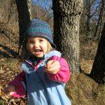 Ein Mädchen zeigt voller Freude was sie im Wald gefunden hat