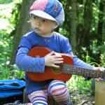 Ein Kind in bunter Kleidung spielt sitzend auf der Gitarre im Wald